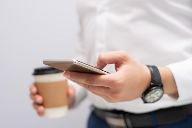 Primo piano del messaggio mandante un sms della mano maschio sul telefono cellulare Foto Gratuite