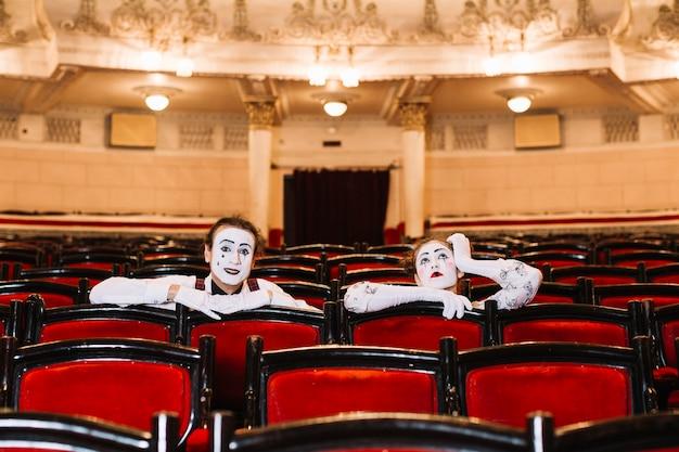 Primo piano del mimo femminile e maschio che si siede sulla sedia del bracciolo nell'auditorium Foto Gratuite