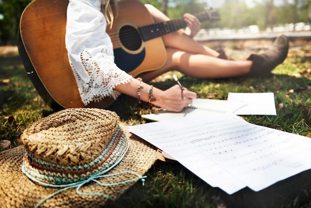 Primo piano del musicista della donna che si siede comporre musica nel parco Foto Gratuite