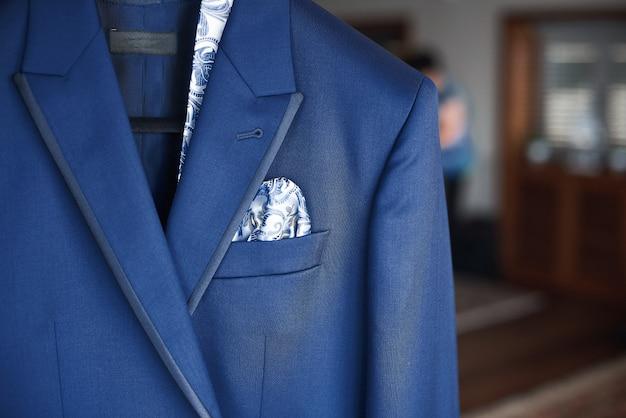 Primo piano del nuovo vestito blu e cravatta dello sposo appeso su un gancio Foto Premium