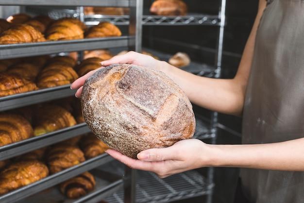 Primo piano del panettiere femminile che tiene pagnotta rustica davanti agli scaffali al forno Foto Gratuite