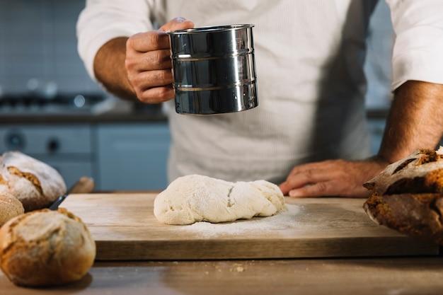 Primo piano del panettiere maschile che setaccia la farina di grano attraverso il setaccio in acciaio sopra la pasta per impastare Foto Gratuite