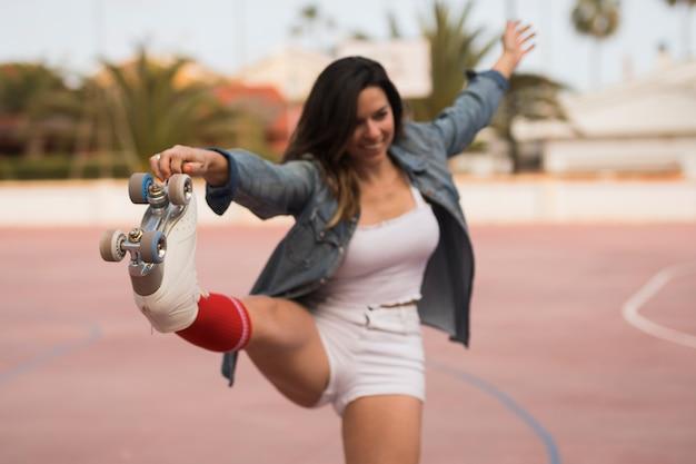 Primo piano del pattino da portare della giovane donna che allunga la sua gamba Foto Gratuite