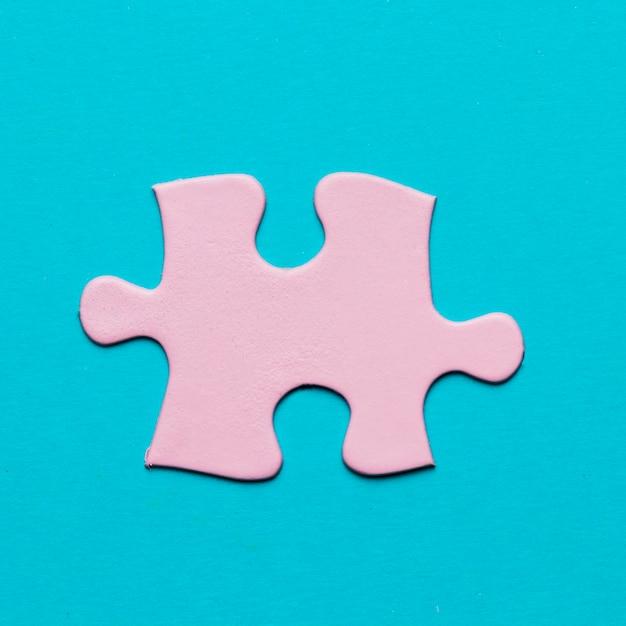 Primo piano del pezzo rosa del puzzle su fondo blu Foto Gratuite