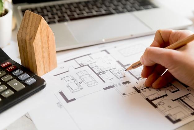 Primo piano del piano di disegno della mano della persona sulla stampa blu con il computer portatile; modello di casa e calcolatrice Foto Gratuite