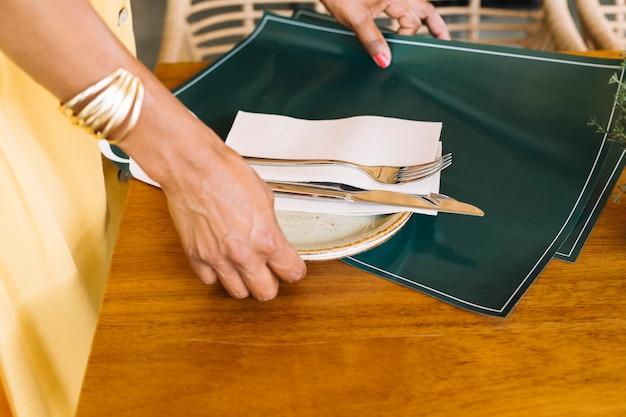 Primo piano del piatto della holding della mano della donna; posate e tovaglietta dal tavolo di legno Foto Gratuite