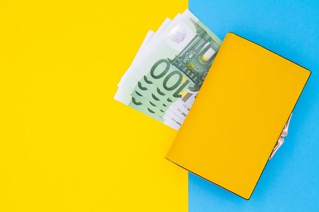 Primo piano del portafoglio giallo con 100 banconote in euro su un tavolo colorato Foto Premium