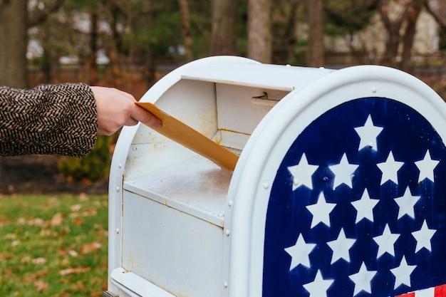 Primo piano del postino che mette la bandiera americana della cassetta delle lettere delle lettere Foto Premium