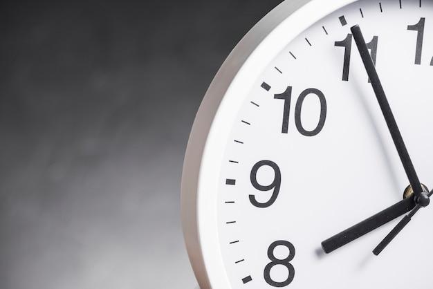 Primo piano del quadrante dell'orologio su sfondo grigio Foto Gratuite