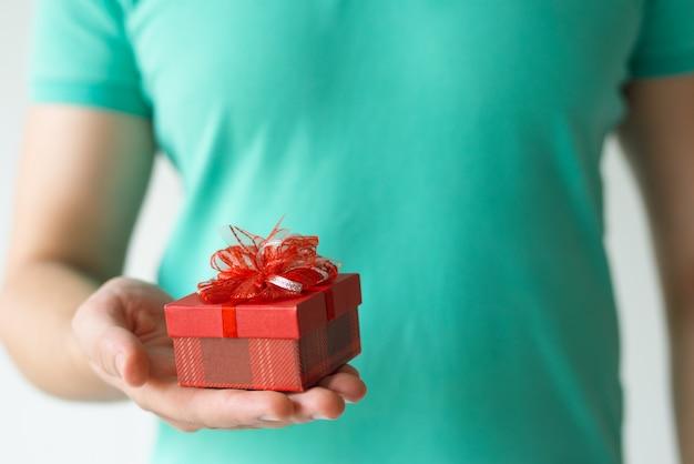 Primo piano del ragazzo che tiene piccolo contenitore di regalo rosso sul palmo Foto Gratuite