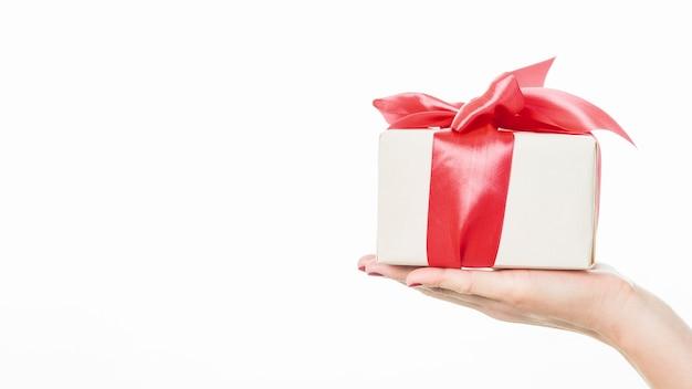 Primo piano del regalo della holding della mano di una donna su priorità bassa bianca Foto Gratuite