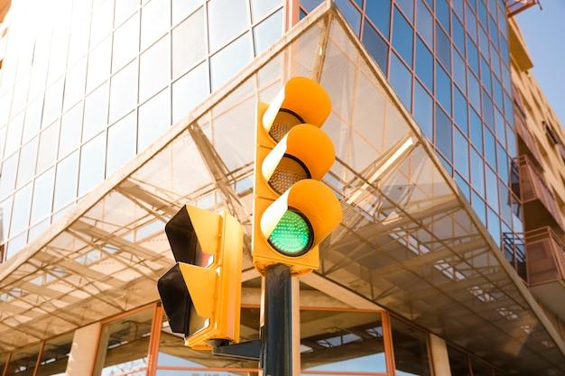 Primo piano del semaforo verde vicino al moderno edificio aziendale Foto Gratuite