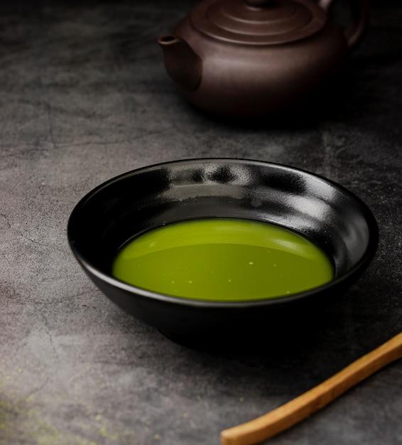 Primo piano del tè di matcha in ciotola con la teiera Foto Gratuite