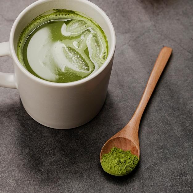 Primo piano del tè di matcha in tazza con il cucchiaio Foto Gratuite
