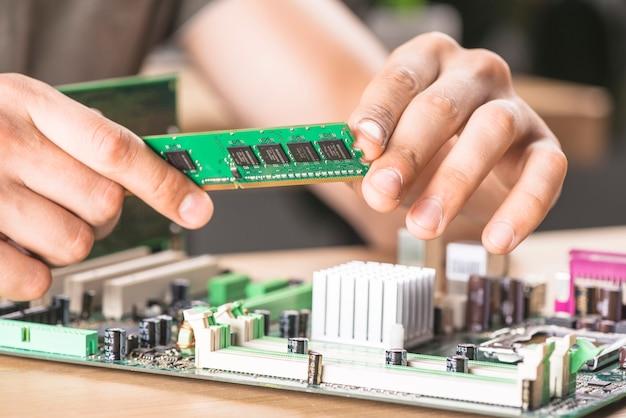 Primo piano del tecnico it maschile che installa la memoria ram nella scheda madre Foto Gratuite