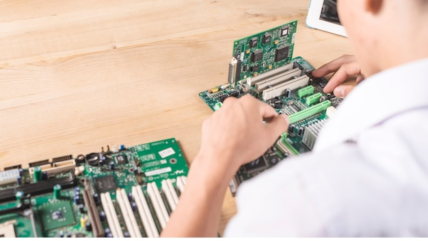 Primo piano del tecnico maschio che ripara la scheda madre moderna del pc sulla tavola di legno Foto Gratuite