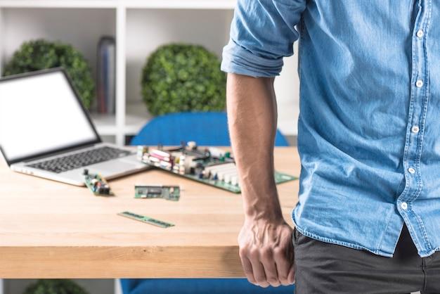 Primo piano del tecnico maschio che si appoggia al bordo della tabella con attrezzature del computer portatile e dell'hardware Foto Gratuite