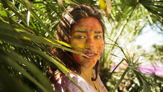 Primo piano del viso della donna coperto di polvere di colore holi in piedi vicino alle piante Foto Gratuite