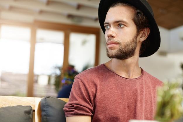 Primo piano del volto del bel giovane modello con barba sfocata in copricapo alla moda e t-shirt con maniche arrotolate che guarda lontano mentre posa all'interno Foto Gratuite