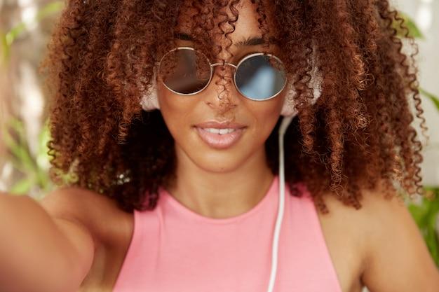 Primo piano del volto di una giovane donna di razza mista nera in tonalità alla moda, fa selfie, indossa occhiali da sole alla moda, ha una pelle scura e sana. ragazza hipster vestita casualmente, gode di buon riposo e divertimento Foto Gratuite