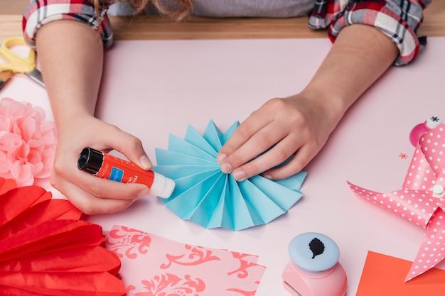 Primo piano dell'artista femminile che attacca il fan di carta di origami blu Foto Gratuite