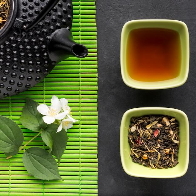 Primo piano dell'erba secca del tè e del fiore bianco del gelsomino Foto Gratuite