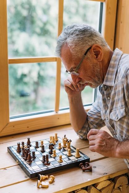 Primo piano dell'uomo anziano che gioca a scacchi sul davanzale della finestra Foto Gratuite