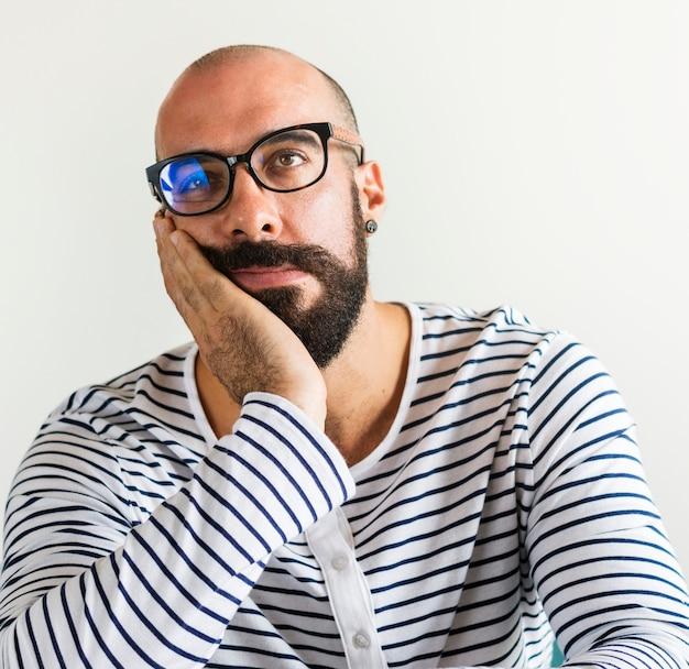 Primo piano dell'uomo barbuto che sembra annoiato Foto Gratuite