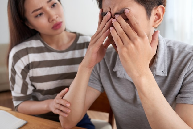 Primo piano dell'uomo che affronta le sfide finanziarie confortate da sua moglie Foto Gratuite