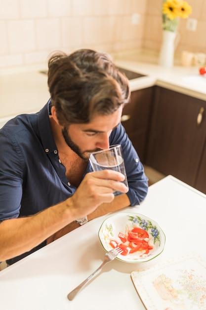 Primo piano dell'uomo che beve bicchiere d'acqua in cucina Foto Gratuite