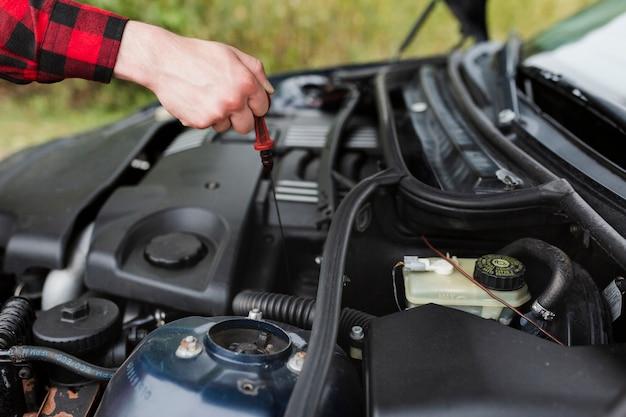 Primo piano dell'uomo che controlla olio per motori Foto Gratuite