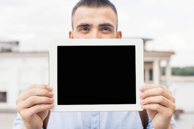 Primo piano dell'uomo che mostra compressa digitale ad all'aperto Foto Gratuite