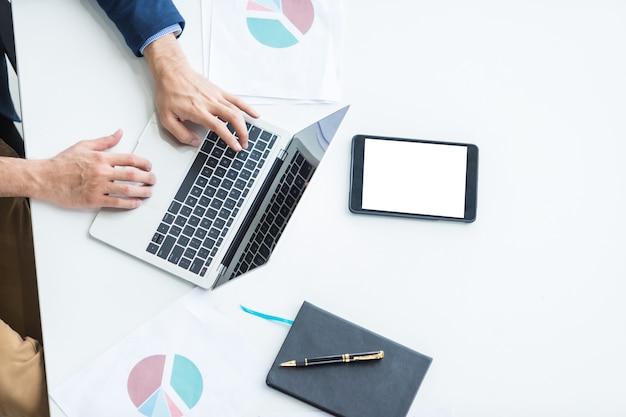 Primo piano dell'uomo d'affari che lavora con la tastiera di battitura a mano sul computer portatile Foto Premium