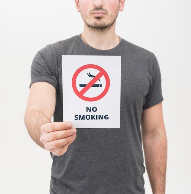 Primo piano dell'uomo in maglietta grigia che mostra segno non fumatori contro fondo bianco Foto Gratuite