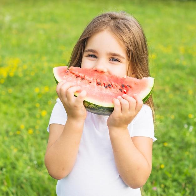 Primo piano della bambina che mangia anguria che sta nel parco Foto Gratuite