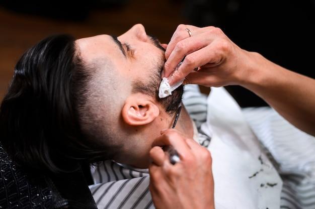 Primo piano della barba del cliente di taglio del barbiere di vista laterale Foto Gratuite