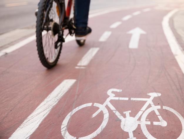 Primo piano della bicicletta che guida la bicicletta sulla strada con il segno della pista ciclabile Foto Gratuite