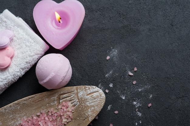 Primo piano della bomba del bagno con la candela accesa rosa Foto Premium