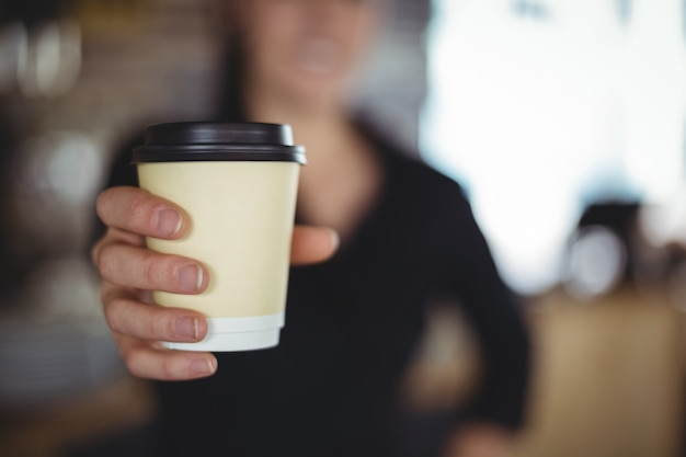 Primo piano della cameriera di bar che sta con la tazza di caffè eliminabile Foto Gratuite