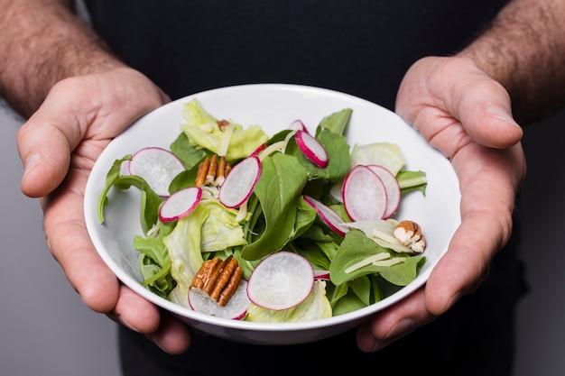 Primo piano della ciotola della holding dell'uomo di insalata in mani Foto Gratuite