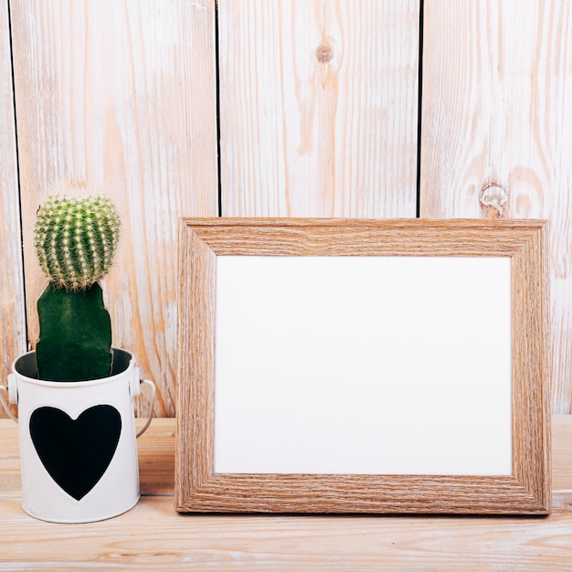 Primo piano della cornice in bianco e pianta succulente con heartshape sul vaso Foto Gratuite