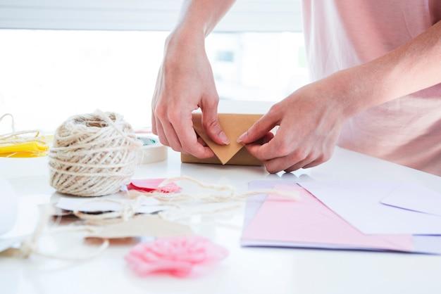 Primo piano della donna che avvolge il contenitore di regalo sulla tavola Foto Gratuite