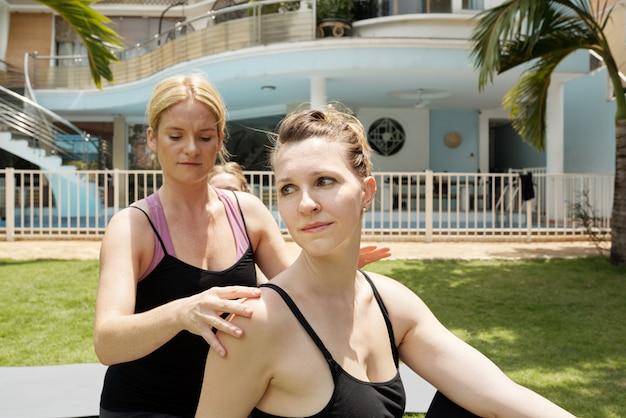 Primo piano della donna che fa yoga con l'istruttore personale nell'iarda anteriore all'aperto con il grande palazzo dietro Foto Gratuite