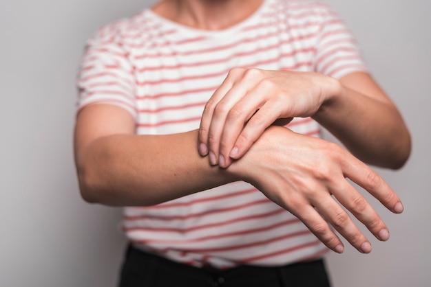 Primo piano della donna che ha dolore al polso che sta contro il fondo grigio Foto Gratuite