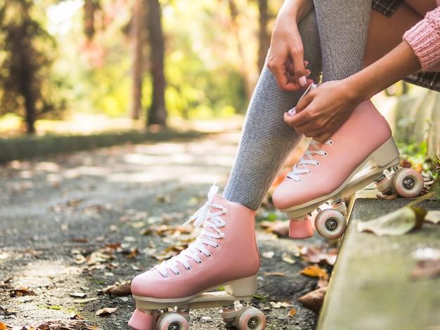 Primo piano della donna che lega laccetto sul pattino a rotelle in calzini Foto Gratuite