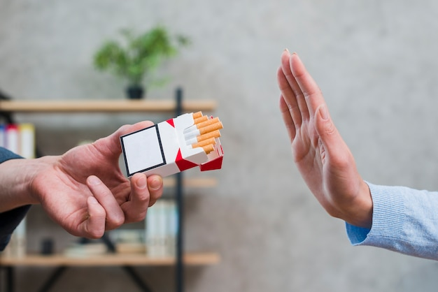 Primo piano della donna che rifiuta le sigarette offerte dal suo collega Foto Gratuite