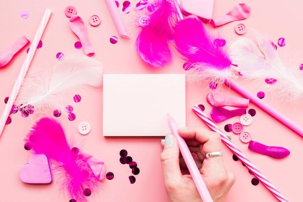 Primo piano della donna che scrive il blocco note con penna e oggetti decorativi su sfondo rosa Foto Gratuite