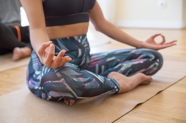 Primo piano della donna che si tiene per mano nel gesto di mudra alla classe di yoga Foto Gratuite
