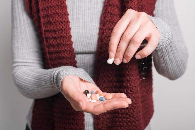 Primo piano della donna che tiene le pillole variopinte Foto Gratuite