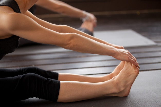 Primo piano della donna degli yogi nella posa di paschimottanasana Foto Gratuite